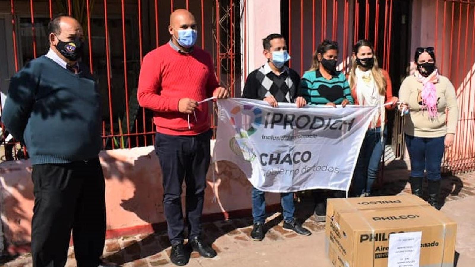 Equipo del IPRODICH haciendo entrega de un aire acondicionado a un beneficiario