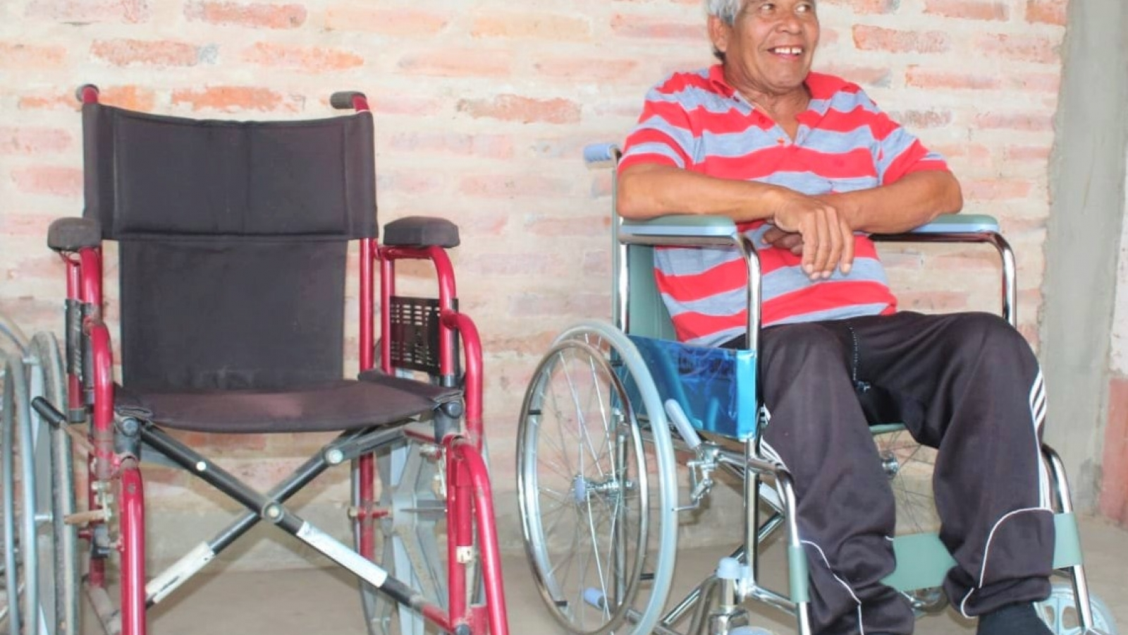Persona con discapacidad sentada en su nueva silla de ruedas