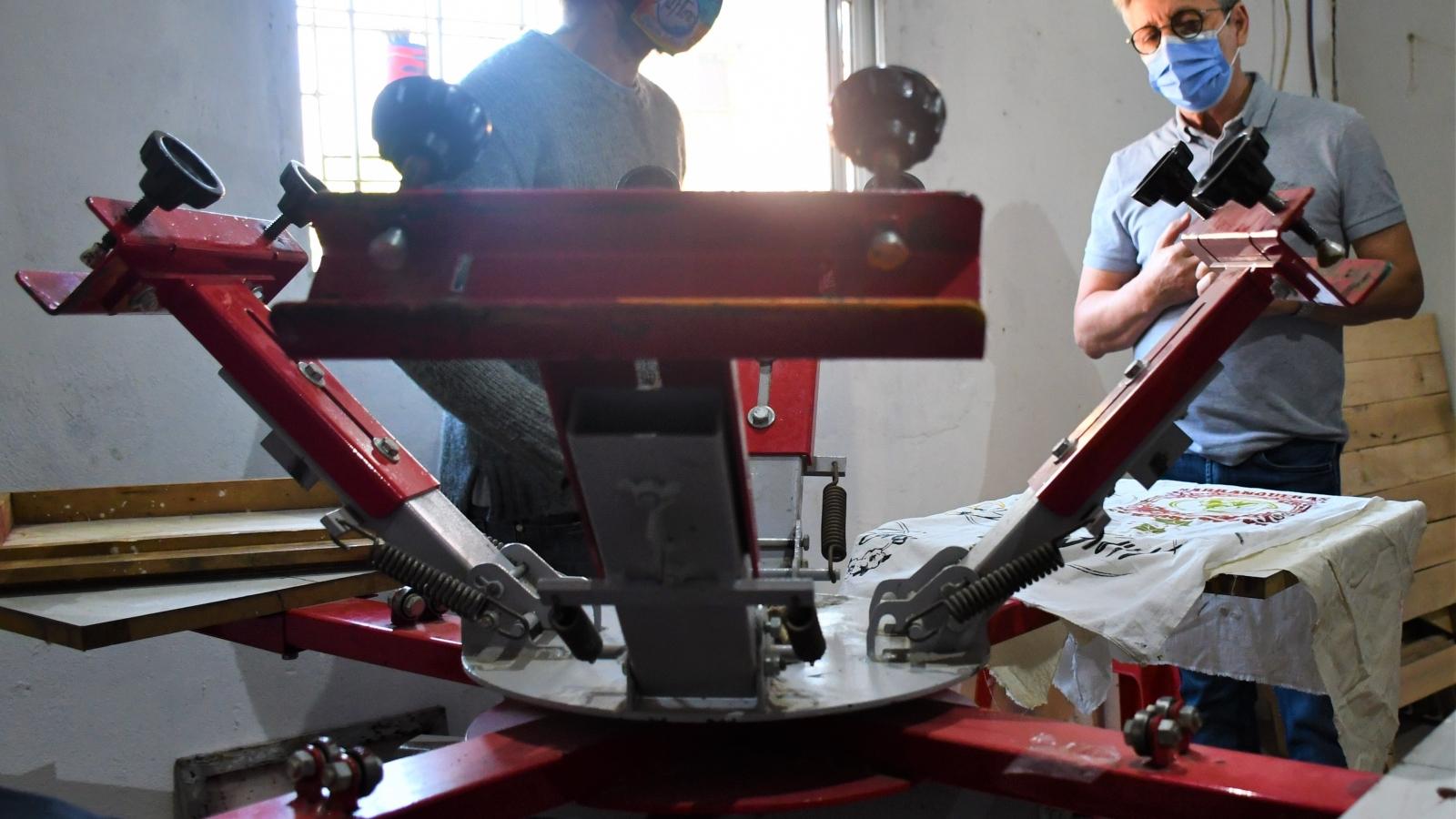 Lorenzo frente a una máquina de serigrafía