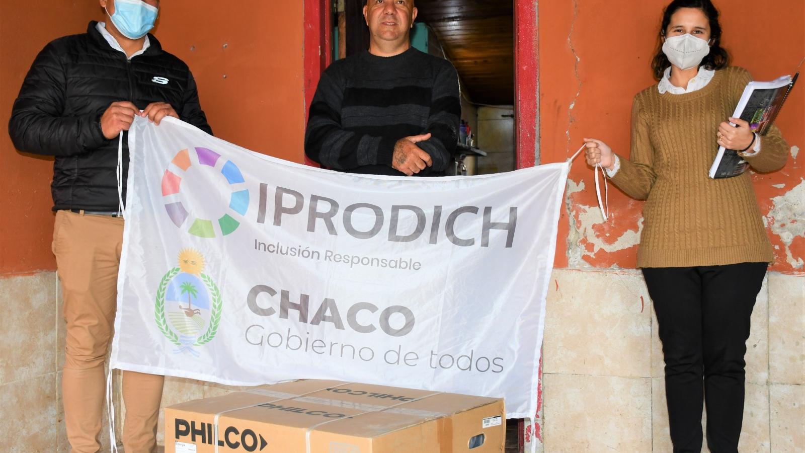 Trabajadores del IPRODICH entregando un aire acondicionado a beneficiario